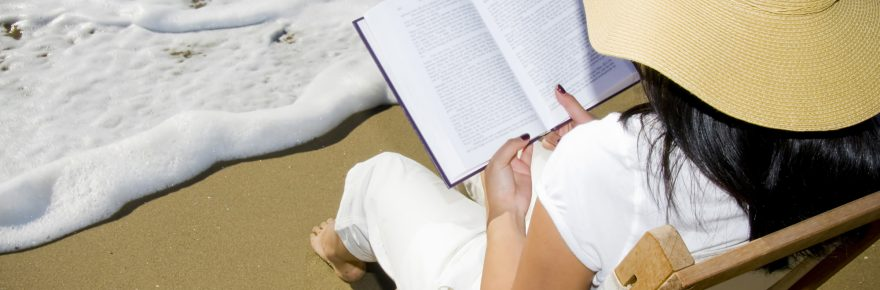 Woman reading book in chair on beach