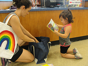 Kennedy Stith chooses her prize for completing 1,000 Books Before Kindergarten as her mom, Rachel Stith, helps.